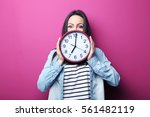 young woman holding a clock on...   Shutterstock . vector #561482119