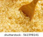 Small photo of Brown sugar (Demerara) background with wooden spoon.