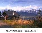 Pretty panorama with wooden mountain hut and the Karwendel mountain range in the Austria / Tirol region in the background - stock photo