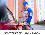 man refueling car's tank by... | Shutterstock . vector #561916669