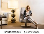 young woman at home sitting on... | Shutterstock . vector #561919021