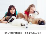 Stock photo portrait of happy young women and caucasian shepherd puppies dogs 561921784