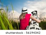 Stock photo beautiful young woman in hat sitting in grass with her dalmatian dog pet with their backs to camera 56194342