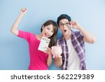 young couple hold pink pig bank ... | Shutterstock . vector #562229389
