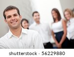 Business man at the office with a group behind him - stock photo