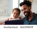 father and son sitting on sofa... | Shutterstock . vector #562358359