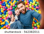 Small photo of Cheerful bearded dad and little son talking selfie at pool with colorful balls