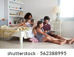 family with baby sitting in... | Shutterstock . vector #562388995