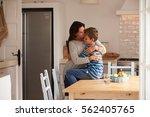 son sitting on kitchen table... | Shutterstock . vector #562405765