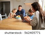 family using digital devices at ... | Shutterstock . vector #562405771