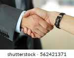 businessman and woman shake... | Shutterstock . vector #562421371