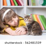 Stock photo happy little girl with her kitten at home at home 562481539