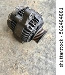 Small photo of Damage dirty vehicle alternator parts on garage concrete floor.