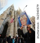 Small photo of NEW YORK CITY - JANUARY 21, 2017: A woman passes by St. Patrick's Cathedral on 5th Ave. with a Hilary Clinton sign, on her way to Trump Tower, during the Women's March in Manhattan.