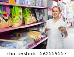 Stock photo female shop assistant offering food for pets in pet store 562559557