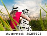 Stock photo beautiful young woman in hat sitting in grass with her dalmatian dog pet with their backs to camera 56259928
