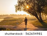 Stock photo the man walking the dog early in the morning by the river 562654981