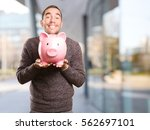 happy young man holding a piggy ... | Shutterstock . vector #562697101