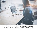 Small photo of Account manager working process.Young business woman work with new startup project in office.Analyze document, plans.Modern laptop on wood table, papers, documents.Horizontal, blurred, flare