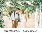 bride and groom hugging at the... | Shutterstock . vector #562752961