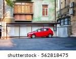 Small photo of lonely red car is waiting for his master driver in the empty courtyard green multi-storey old house in a sunny day, empty car parked on a makeshift yard parking