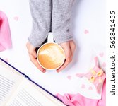 Small photo of Female hands in grey knit holding cup of cappuccino. Gift alike dessert with heart shape sprinkles. Opened book. Top view. Valentines concept. Pink textile. Square