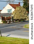 Small photo of Ronks, PA - June 1, 2013: An Amish farmer uses a team of draft horses to pull a hay wagon with metal wheels on a road.