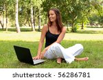 Beautiful young woman sits on a grass in a park with the laptop. - stock photo