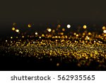 sprinkle gold dust on a black... | Shutterstock . vector #562935565