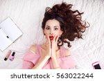 shocked brunette lying on bed... | Shutterstock . vector #563022244