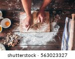 hands kneading raw dough on... | Shutterstock . vector #563023327