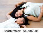 lesbian couple lying on wooden... | Shutterstock . vector #563089201