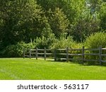 This is a shot of a wooden fence against a background of green. - stock photo