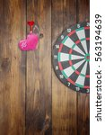 Small photo of Darts, accurate hit the target, the dart in the heart on wooden background