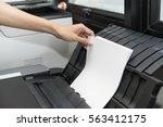 woman hand putting a sheet of... | Shutterstock . vector #563412175