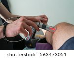 laser therapy on a knee used to ... | Shutterstock . vector #563473051