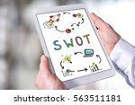 man holding a tablet showing... | Shutterstock . vector #563511181
