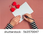 Small photo of Woman writing love letter or romantic poem for Valentines day, top view of female hands