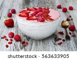 Small photo of Pink acai, maca powder smoothie bowl topped with sliced strawberries, raspberries and goji berries. Copy space. Valentines Day superfood aphrodisiac meal