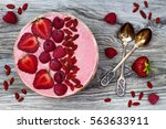 Small photo of Pink acai, maca powder smoothie bowl topped with sliced strawberries, raspberries and goji berries. Flat lay, copy space. Valentines Day superfood aphrodisiac meal