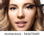 woman doing her makeup... | Shutterstock . vector #563670685