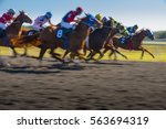 Stock photo horse race colorful bright sunlit slow shutter speed motion effect fast moving thoroughbreds 563694319