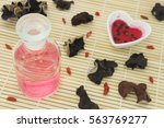 Small photo of Elixir of love, Prepare red philter in heart bowl, finished product in glass bottle and ingredient on bamboo mat.