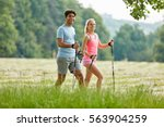 young couple hiking in the... | Shutterstock . vector #563904259