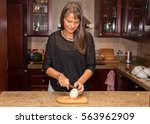 middle aged woman cutting a...