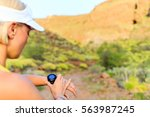 Small photo of Woman runner checking the elevation on sports watch, smartwatch with altimeter app in summer mountains. Young girl training and running on mountain trail in the morning.