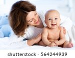 mother and child on a white bed.... | Shutterstock . vector #564244939