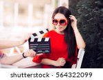 Small photo of Actress with Oversized Sunglasses Shooting Movie Scene - Diva in red dress and big shades starring in an artistic film