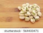 pistachio nuts on wooden... | Shutterstock . vector #564433471