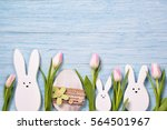 Stock photo easter background with white rabbits pink tulips and easter egg top view 564501967
